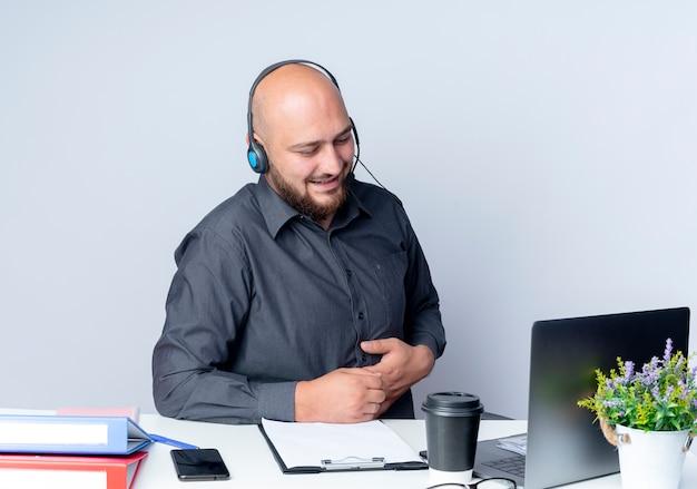 Zadowolony młody łysy mężczyzna call center sobie zestaw słuchawkowy siedzi przy biurku z narzędzi pracy patrząc na laptopa kładąc rękę na brzuchu na białym tle