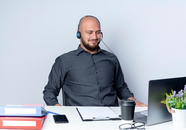Zadowolony młody łysy mężczyzna call center sobie zestaw słuchawkowy siedzi przy biurku z narzędzi pracy patrząc na laptopa na białym tle