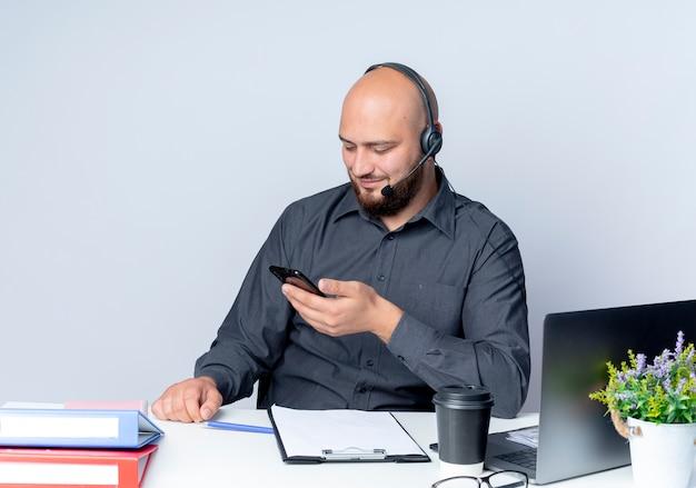 Zadowolony młody łysy mężczyzna call center sobie zestaw słuchawkowy siedzi przy biurku z narzędziami pracy, trzymając i patrząc na telefon komórkowy na białym tle