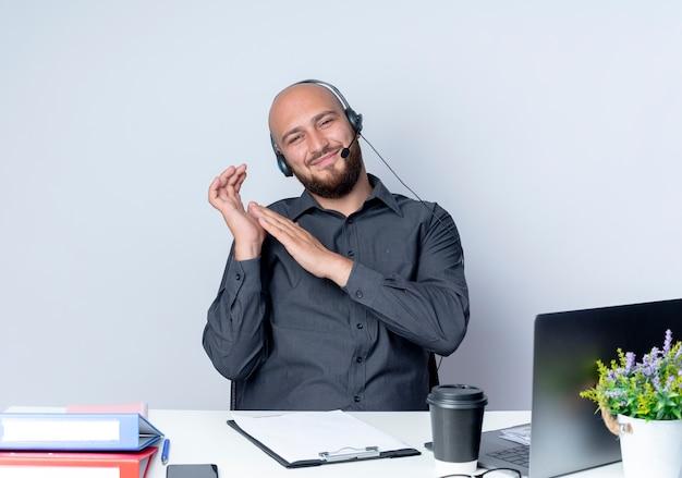 Zadowolony młody łysy mężczyzna call center sobie zestaw słuchawkowy siedzi przy biurku z narzędziami pracy, trzymając rękę w pobliżu innego na białym tle