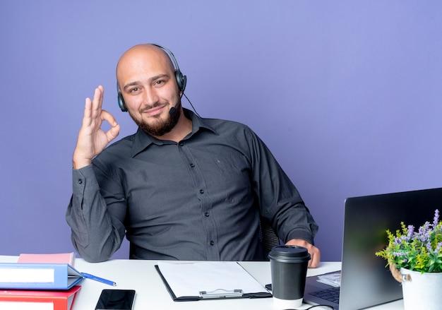 Zadowolony młody łysy mężczyzna call center sobie zestaw słuchawkowy siedzi przy biurku z narzędziami roboczymi robi ok znak na białym tle na fioletowym tle