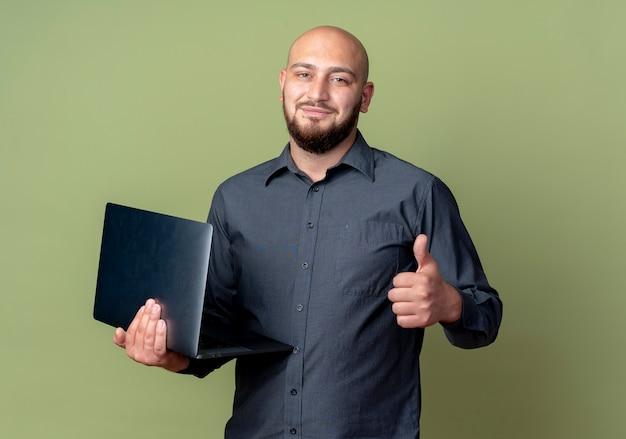 Zadowolony młody łysy mężczyzna call center trzyma laptopa i pokazuje kciuk w górę na białym tle na oliwkowym tle z miejsca na kopię