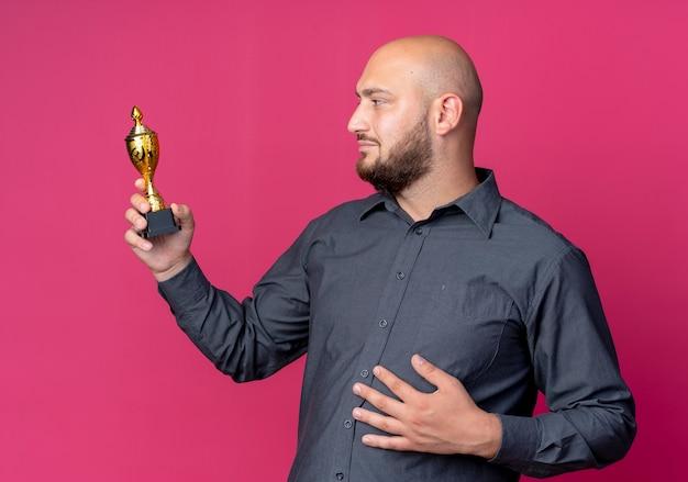 Zadowolony młody łysy mężczyzna call center trzymając i patrząc na puchar zwycięzcy i kładąc rękę na brzuchu na białym tle na szkarłatnym tle