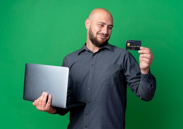 Zadowolony młody łysy mężczyzna call center trzymając laptop i kartę kredytową patrząc na kartę na białym tle na zielonym tle