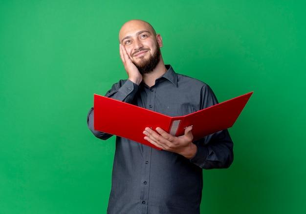 Zadowolony młody łysy mężczyzna call center trzymając otwarty folder kładąc rękę na twarzy patrząc w górę na białym tle na zielonym tle z miejsca na kopię
