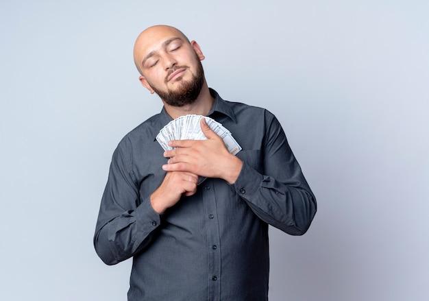 Zadowolony młody łysy mężczyzna call center trzymając pieniądze z zamkniętymi oczami na białym tle na białym tle z miejsca na kopię