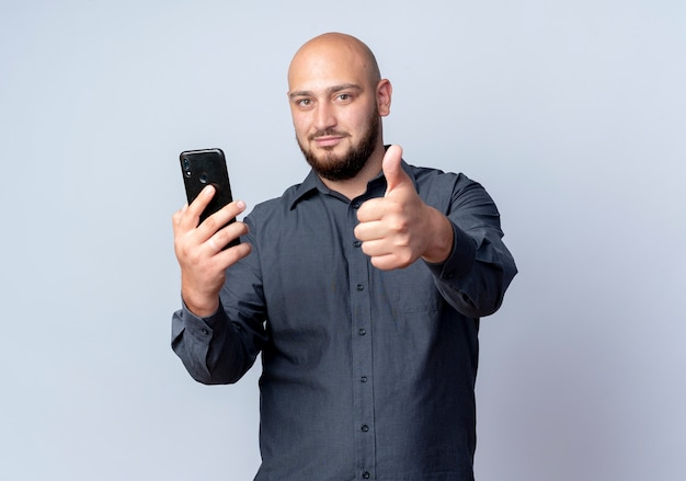 Zadowolony młody łysy mężczyzna call center trzymając telefon komórkowy i pokazując kciuk do góry na białym tle na białym tle z miejsca na kopię