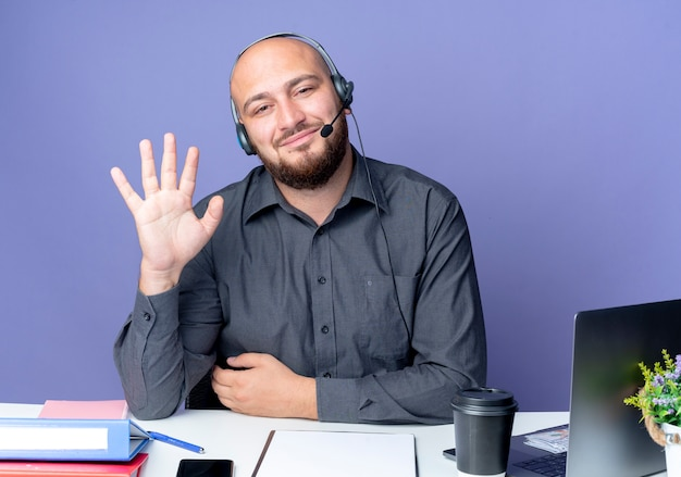 Zadowolony młody łysy mężczyzna z call center w zestawie słuchawkowym siedzi przy biurku z narzędziami pracy, wskazując cześć na aparat na białym tle na fioletowym tle