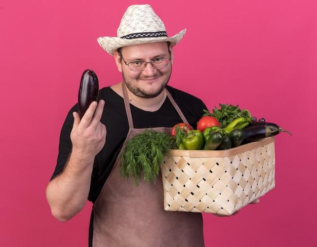 Zadowolony młody mężczyzna ogrodnik w kapeluszu ogrodniczym trzymający kosz warzyw z bakłażanem odizolowany na różowej ścianie
