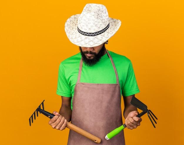 Zadowolony młody ogrodnik afro-amerykański facet w kapeluszu ogrodniczym, trzymający i patrzący na grabie z motyką na białym tle na pomarańczowej ścianie