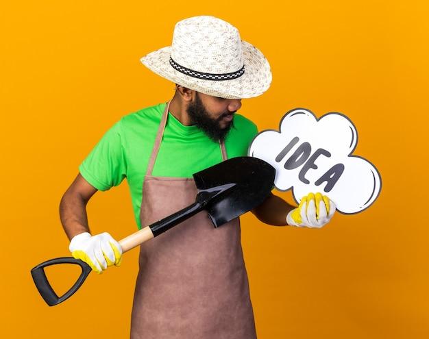 Zadowolony młody ogrodnik afroamerykański facet w kapeluszu ogrodniczym i rękawiczkach, trzymający łopatę z bańką pomysłów