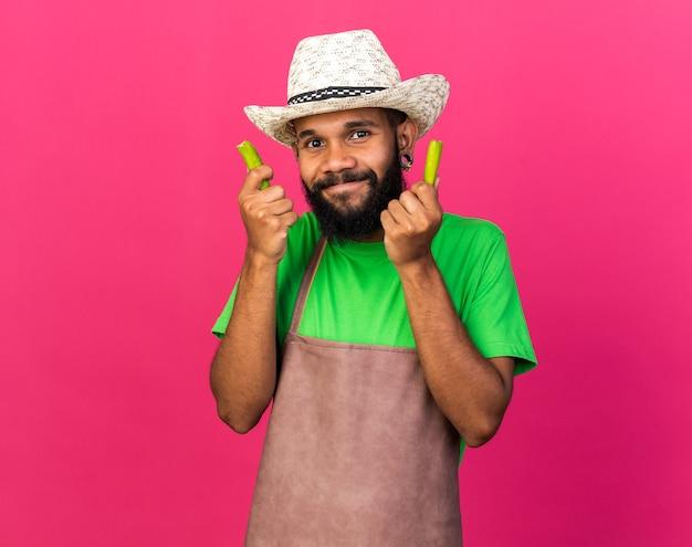 Zadowolony młody ogrodnik afroamerykański facet w kapeluszu ogrodniczym trzymający zepsuty pieprz