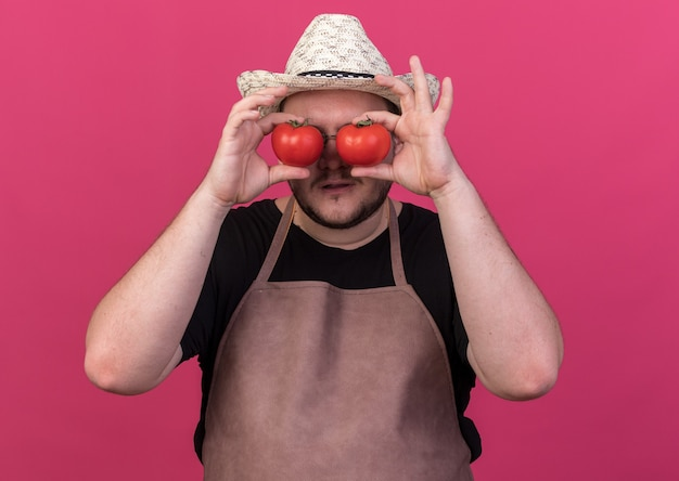 Zadowolony młody ogrodnik męski w kapeluszu ogrodniczym pokazujący gest wyglądu z pomidorami na białym tle na różowej ścianie