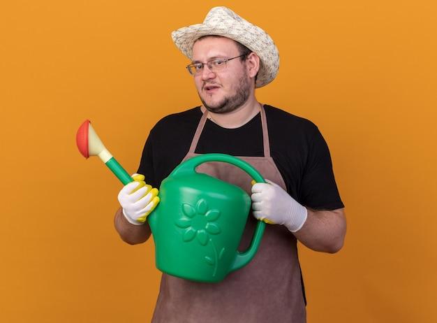 Zadowolony młody ogrodnik mężczyzna w kapeluszu ogrodniczym i rękawiczkach trzyma konewkę na białym tle na pomarańczowej ścianie