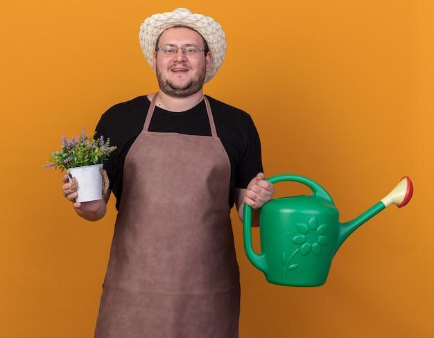 Zadowolony młody ogrodnik mężczyzna w kapeluszu ogrodniczym i rękawiczkach trzyma konewkę z kwiatkiem w doniczce na białym tle na pomarańczowej ścianie