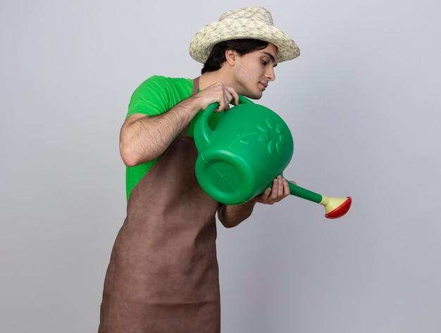 Zadowolony młody ogrodnik mężczyzna w mundurze w kapeluszu ogrodniczym podlewający z konewką