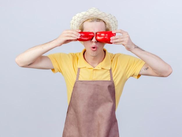 Zadowolony młody ogrodnik ubrany w kombinezon i kapelusz pokazujący czerwoną paprykę zakrywającą oczy uśmiechem
