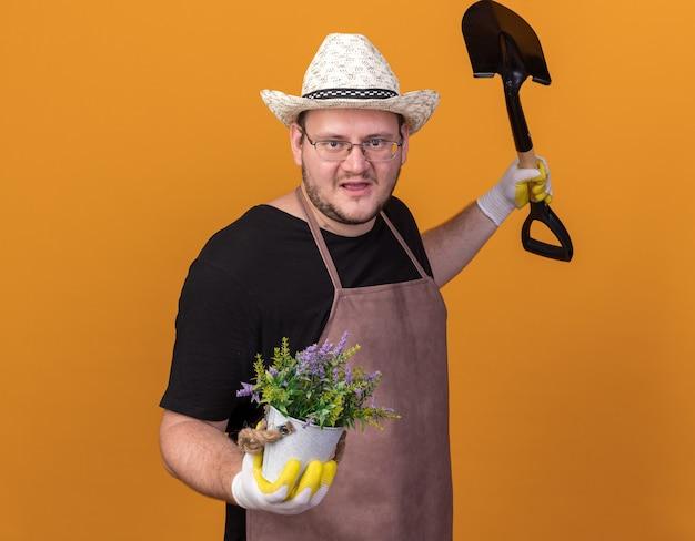 Zadowolony młody ogrodnik w kapeluszu ogrodniczym i rękawiczkach trzymający łopatę z kwiatkiem w doniczce, rozkładający ręce na pomarańczowej ścianie