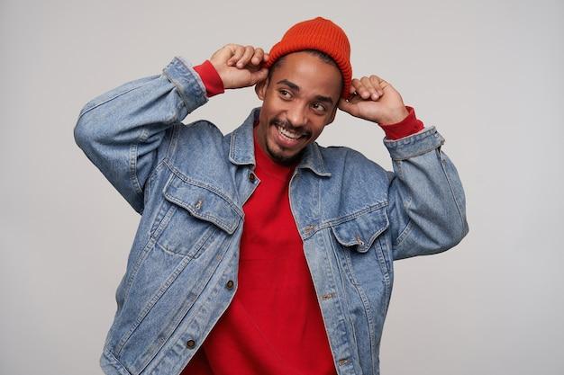 Zadowolony młody, piękny, brodaty, brązowowłosy mężczyzna o ciemnej skórze podnoszący ręce do nakrycia głowy i wyglądający wesoło na bok, ubrany w czerwoną czapkę, sweter i niebieski dżinsowy płaszcz na białej ścianie