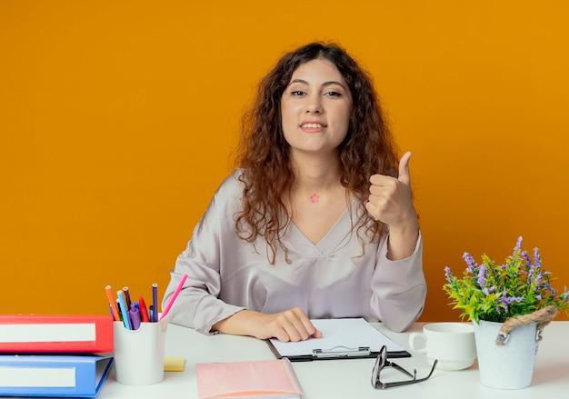 Zadowolony młody pracownik biurowy całkiem żeński siedzi przy biurku z narzędzi biurowych jej kciuk do góry na białym tle na pomarańczowy