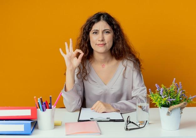 Zadowolony młody pracownik biurowy całkiem żeński siedzi przy biurku z narzędzi biurowych pokazując gest okey samodzielnie na pomarańczowo