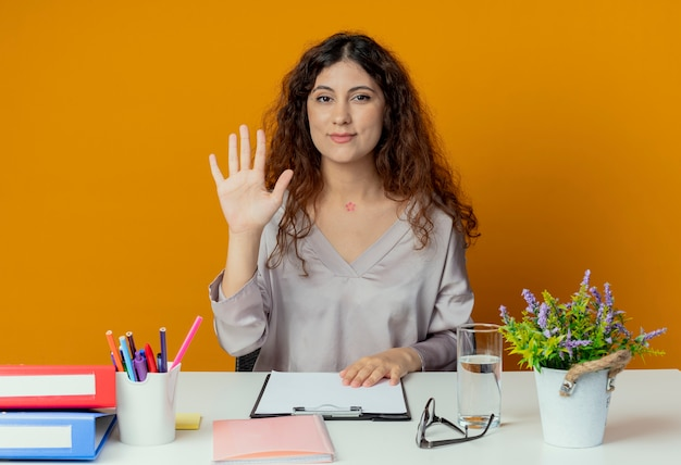 Zadowolony młody pracownik biurowy całkiem żeński siedzi przy biurku z narzędzi biurowych pokazując gest powitania samodzielnie na pomarańczowo