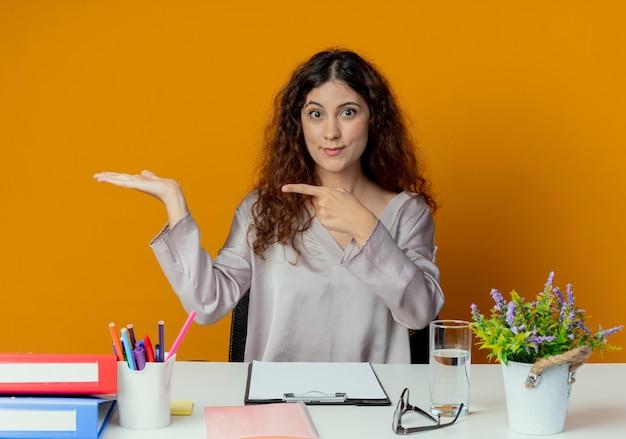 Zadowolony młody pracownik biurowy całkiem żeński siedzi przy biurku z narzędzi biurowych, udając, że trzyma coś odizolowanego na pomarańczowo