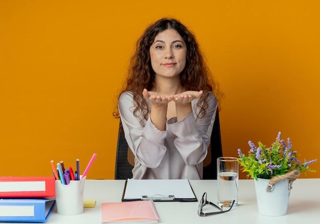 Zadowolony młody pracownik biurowy całkiem żeński siedzi przy biurku z narzędzi biurowych wyciągając ręce do kamery samodzielnie na pomarańczowy