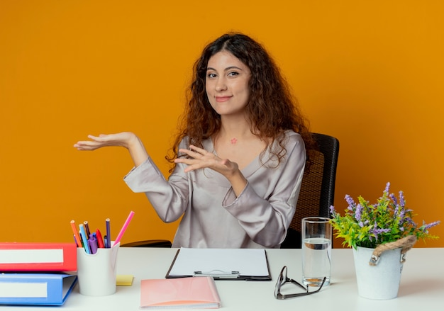 Zadowolony młody pracownik biurowy całkiem żeński siedzi przy biurku z punktów narzędzi pakietu office z rękami na boku na białym tle na pomarańczowy