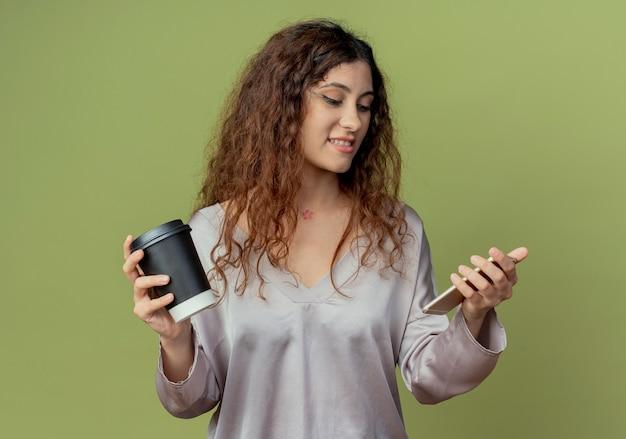 Zadowolony młody pracownik biurowy całkiem żeński trzymając filiżankę kawy i patrząc na telefon w ręku na białym tle na oliwkowej ścianie