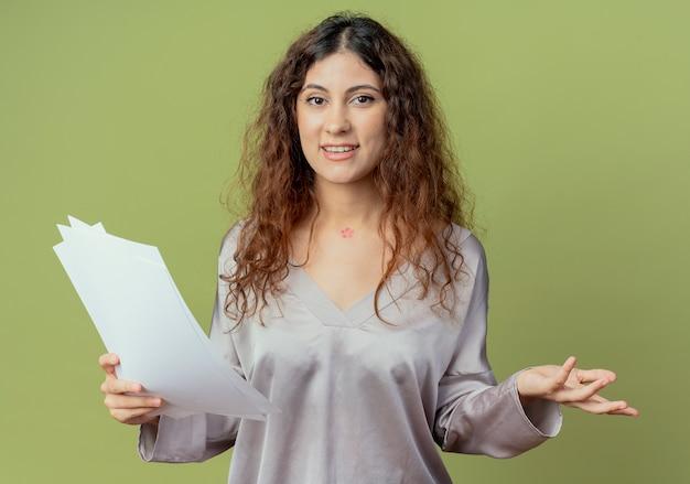 Zadowolony młody pracownik biurowy całkiem żeński trzymając papiery i rozkłada ręce na białym tle na oliwkowej ścianie