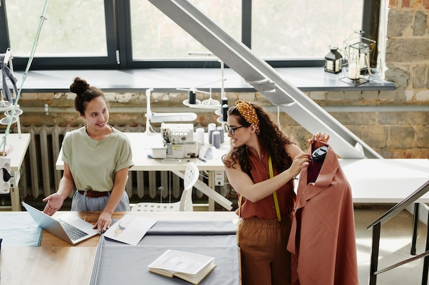 Zadowolony młody projektant mody pokazuje koledze nowe modele lub przedmioty na ekranie laptopa, konsultując się z nią w sprawie wyboru