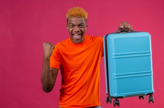 Zadowolony młody przystojny chłopak ubrany w pomarańczowy t-shirt, trzymając walizkę podróżną