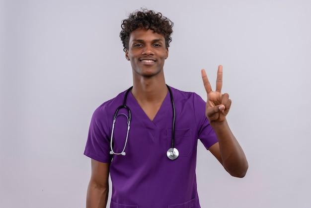 Zadowolony, młody, przystojny, ciemnoskóry lekarz z kręconymi włosami, ubrany w fioletowy mundur ze stetoskopem pokazującym palcami numer dwa