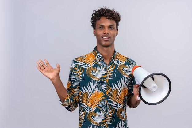 Zadowolony młody przystojny ciemnoskóry mężczyzna z kręconymi włosami w koszulce z nadrukiem liści trzyma megafon na białym tle