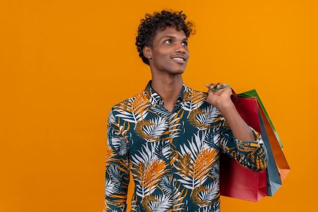 Zadowolony młody przystojny ciemnoskóry mężczyzna z kręconymi włosami w koszulce z nadrukiem w liście uśmiecha się trzymając torby na zakupy, stojąc na pomarańczowym tle