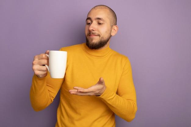 Zadowolony młody przystojny facet trzyma i wskazuje ręką na filiżankę herbaty na białym tle na fioletowej ścianie z miejsca na kopię