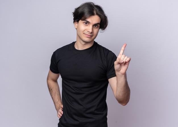 Zadowolony młody przystojny facet ubrany w czarną koszulkę wskazuje na położenie ręki na biodrze na białej ścianie