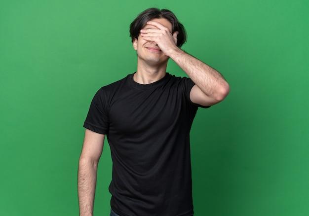 Zadowolony młody przystojny facet ubrany w czarną koszulkę zakryte oczy ręką odizolowaną na zielonej ścianie