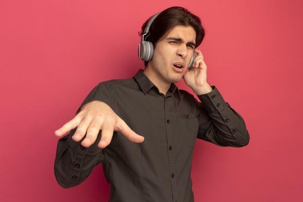 Zadowolony młody przystojny facet ubrany w czarną koszulkę ze słuchawkami pokazujący dj gest na białym tle na różowej ścianie