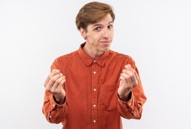 Zadowolony młody przystojny facet ubrany w czerwoną koszulę pokazując gest napiwku