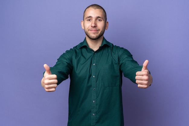 Zadowolony młody przystojny facet ubrany w zieloną koszulę pokazując kciuk do góry