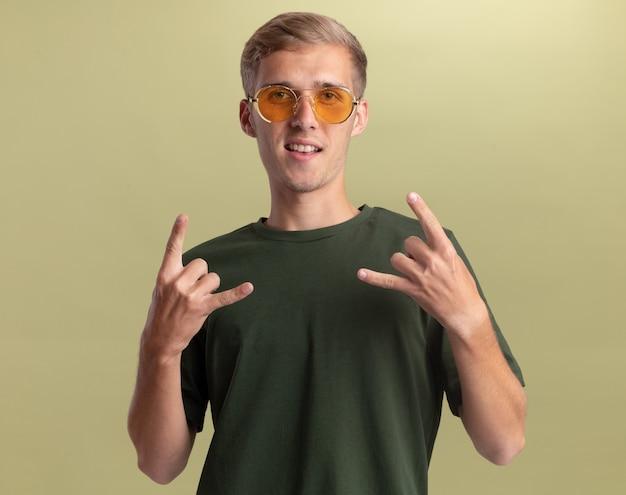 Zadowolony młody przystojny facet ubrany w zieloną koszulę w okularach pokazujący gest kozy na tle oliwkowej ściany
