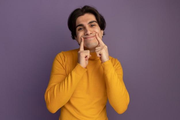 Zadowolony młody przystojny facet ubrany w żółty sweter z golfem robi uśmiechając się palcami odizolowanymi na fioletowej ścianie