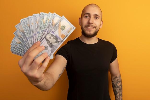 Zadowolony młody przystojny facet w czarnej koszuli wyciągający gotówkę