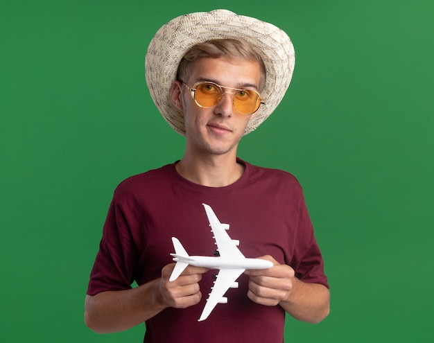 Zadowolony młody przystojny facet w czerwonej koszuli z okularami i kapeluszem, trzymając samolocik na zielonej ścianie
