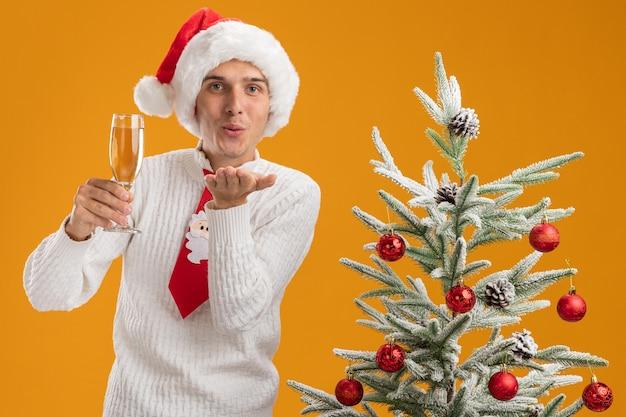Zadowolony młody przystojny facet w świątecznej czapce i krawacie świętego mikołaja, stojący w pobliżu udekorowanej choinki, trzymając kieliszek szampana patrząc w kamerę, wysyłając pocałunek ciosu na białym tle na pomarańczowym tle