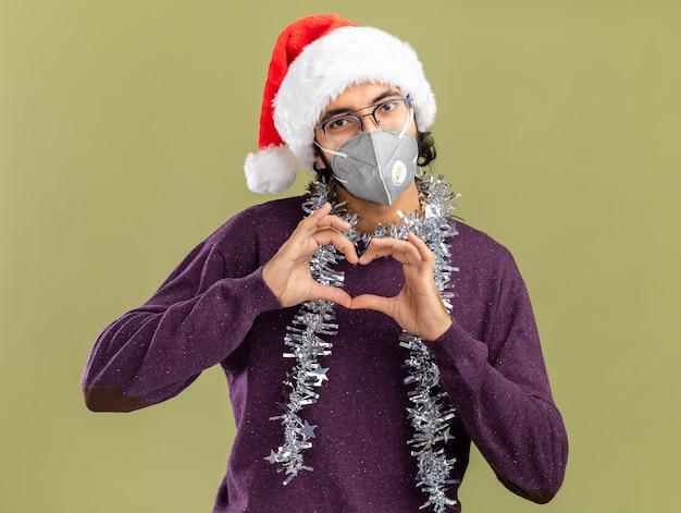 Zadowolony młody przystojny facet w świątecznym kapeluszu i masce medycznej z girlandą na szyi pokazującym gest serca na oliwkowozielonej ścianie