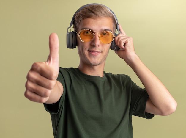 Zadowolony młody przystojny facet w zielonej koszuli z okularami i słuchawkami, pokazując kciuk do góry na białym tle na oliwkowej ścianie