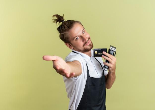 Zadowolony młody przystojny fryzjer trzymający kartę kredytową i maszynkę do strzyżenia włosów i wyciągający rękę z przodu odizolowany na oliwkowej ścianie